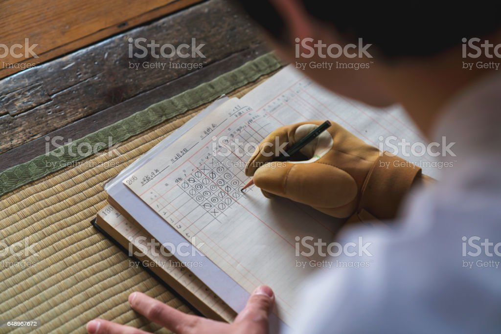 Archer marking scores in a ledger stock photo