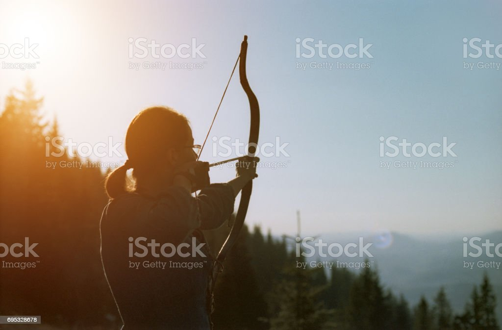 Archer shooting with a bow in the mountains. stock photo
