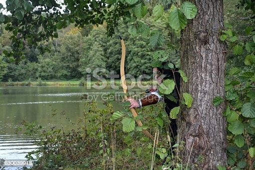 630040004istockphoto Archer stands hidden behind tree  with tense curve 630039918