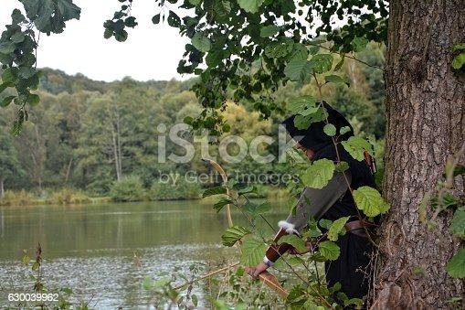 630040004istockphoto Archer  stands hidden behind tree with tense curve 630039962