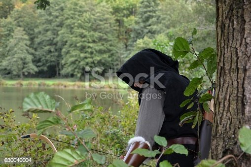 istock Archer stands hidden behind tree with tense curve 630040004