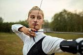 Teenage girl on archery training outdoors.