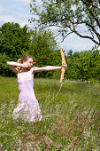 Young woman is shooting with a bow in a high grass surrounded by some trees.See some similar pictures from my portfolio: