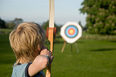 Boy taking part in the sporting activity of archery.  Taking aim at the target
