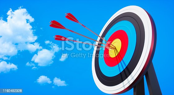Archery target with hits by several arrows with sun against a clear blue sky with little clouds