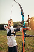Teenage girl on archery training outdoors.