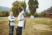 Teenage girl on archery training with her father as a coach.