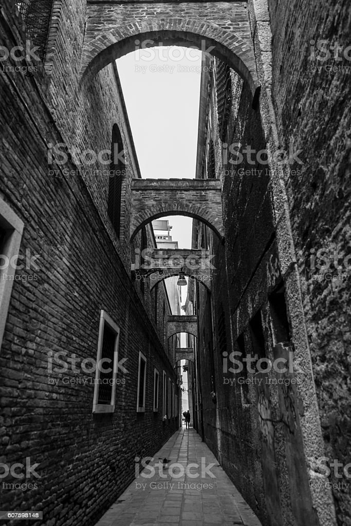 Arches over the narrow street in Venice. stock photo