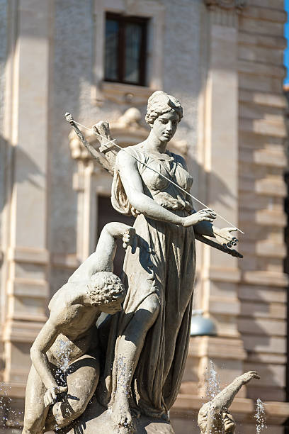 Archimede's square Historic water fountain statue of two people, woman with bow and arrows. artemis stock pictures, royalty-free photos & images