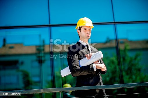 Architect analyzing blueprint plans outdoors