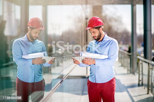 Architect analyzing  plans on digital tablet at outdoors