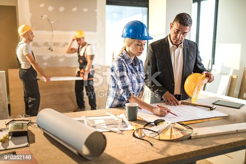 istock Architect and building contractor going through housing plan at construction site. 910352146