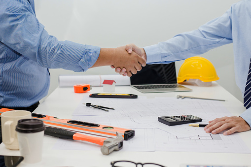 912867216 istock photo Architect and businessman shaking hands meeting discuss a plan about the construction project of real estate. Agreement and are willing to work together. 1015513014