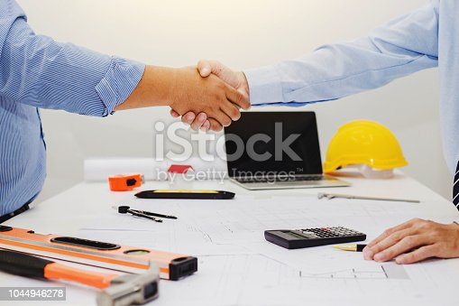 976560476istockphoto Architect and businessman shaking hands meeting discuss a plan about the construction project of real estate. Agreement and are willing to work together. 1044946278