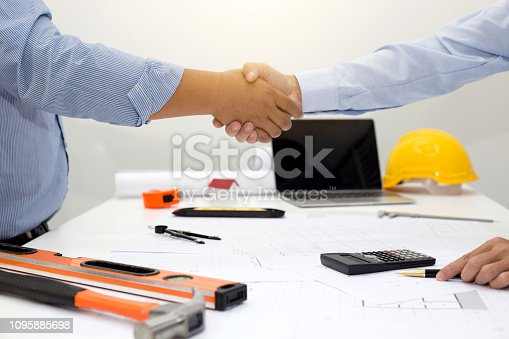 976560476istockphoto Architect and businessman shaking hands meeting discuss a plan about the construction project of real estate. Agreement and are willing to work together. 1095885698