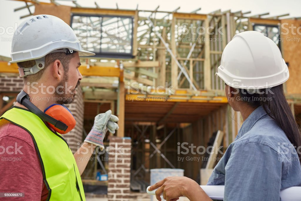 Architect and Construction Manager looking at building at...
