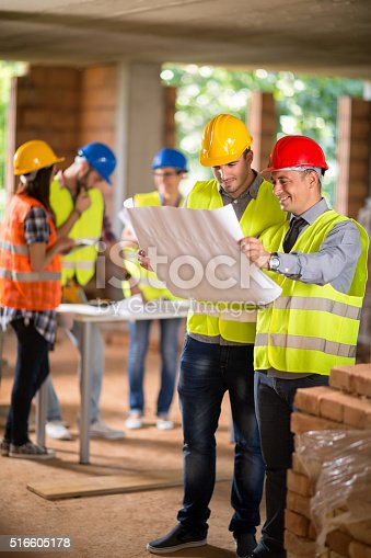 516607254istockphoto Architect and construction worker look blue print 516605178