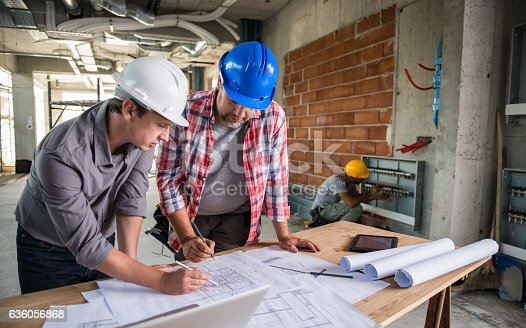 istock Architect And Construction Worker Reviewing Blueprint Together 636056868