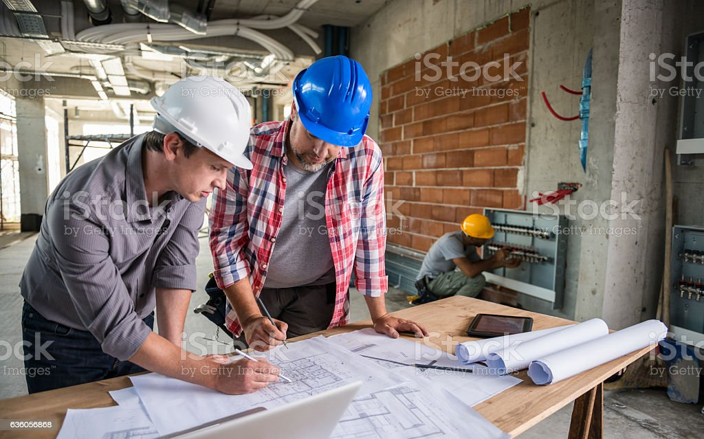 Architect And Construction Worker Reviewing Blueprint Together stock photo