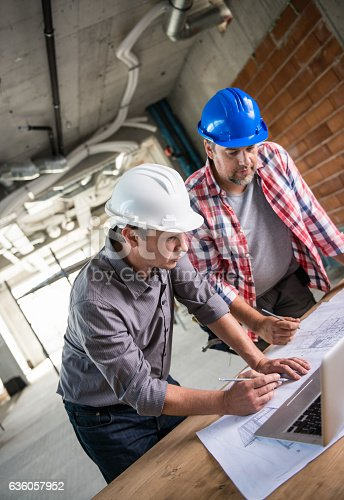 istock Architect And Construction Worker Reviewing Blueprint Together 636057952