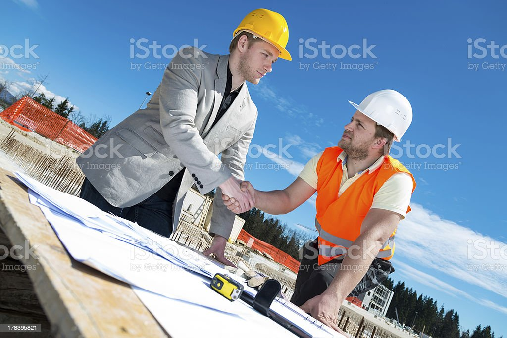 Architect and construction worker shaking hands. royalty-free stock photo