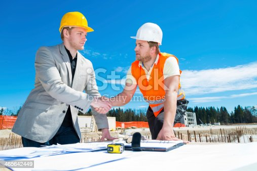 1071990712 istock photo Architect and construction worker shaking hands. 465642449