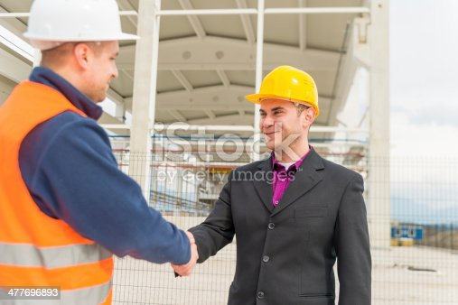 1071990712 istock photo Architect and construction worker shaking hands. 477696893