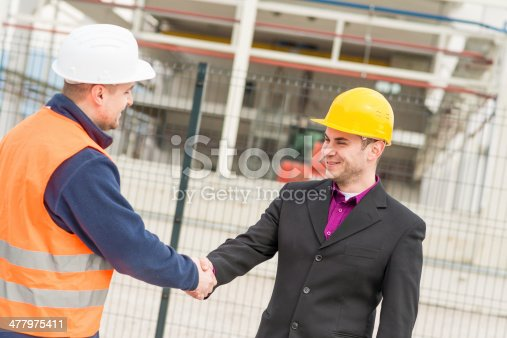 1071990712 istock photo Architect and construction worker shaking hands. 477975411