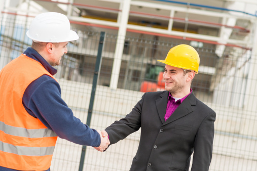 912867216 istock photo Architect and construction worker shaking hands. 477975411