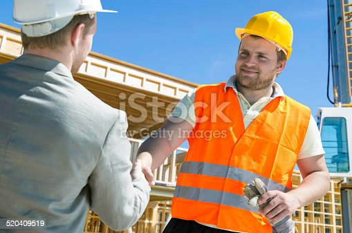 1071990712 istock photo Architect and construction worker shaking hands. 520409519