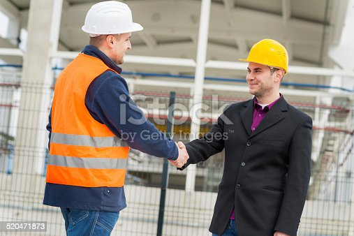 1071990712 istock photo Architect and construction worker shaking hands. 520471873
