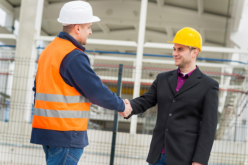 912867216 istock photo Architect and construction worker shaking hands. 520471873