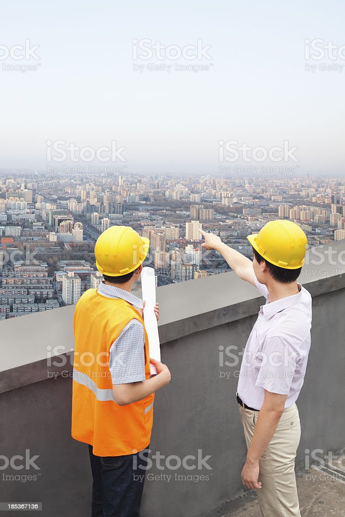 Architect And Construction Worker Talking On Rooftop royalty-free stock photo