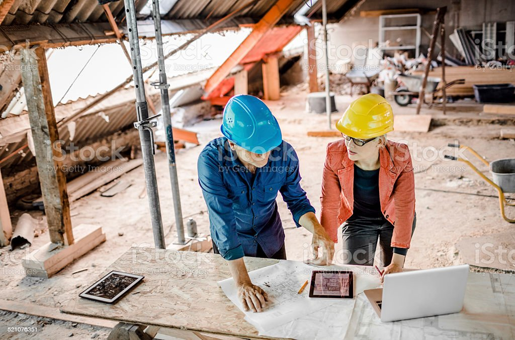 Architect And Construction Worker With Plans, Tablet PC And Laptop stock photo