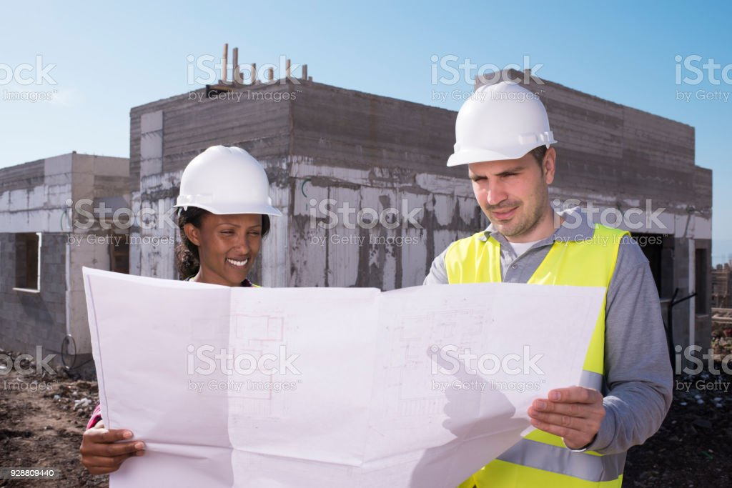 Architect and construction worker checking the progress of their...