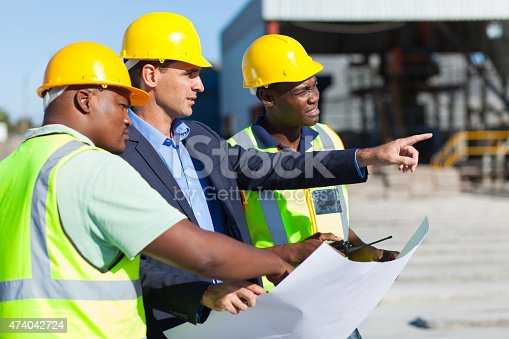 group of architect and construction workers on site with blue print
