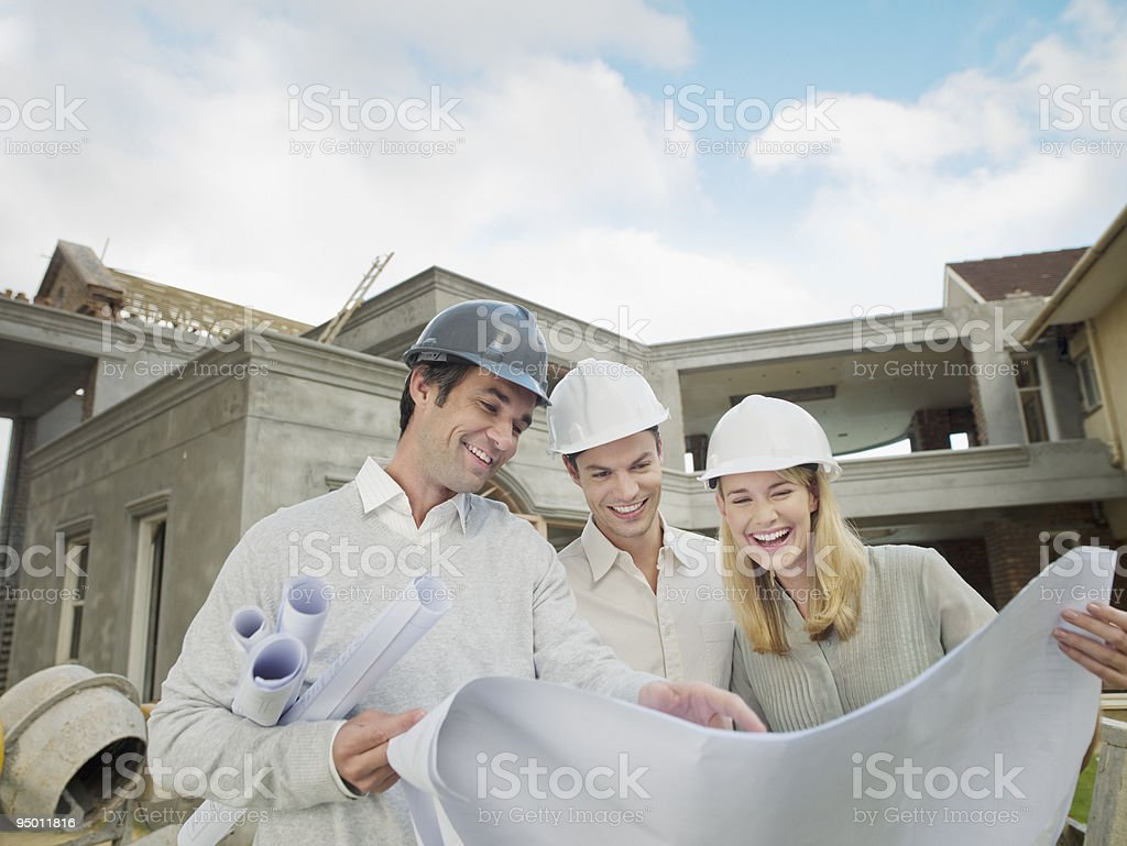 Architect and couple looking at blueprints outside house under construction royalty-free stock photo