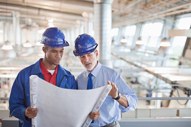 architekt und ingenieur überprüft blueprint in fabrik - baugenehmigung stock-fotos und bilder