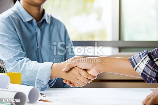 istock Architect and engineer shaking hand in office. Concept building team working on project. Cooperation 828270286