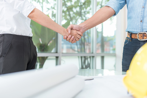 912867216 istock photo Architect and engineer shaking hand in office 817655072
