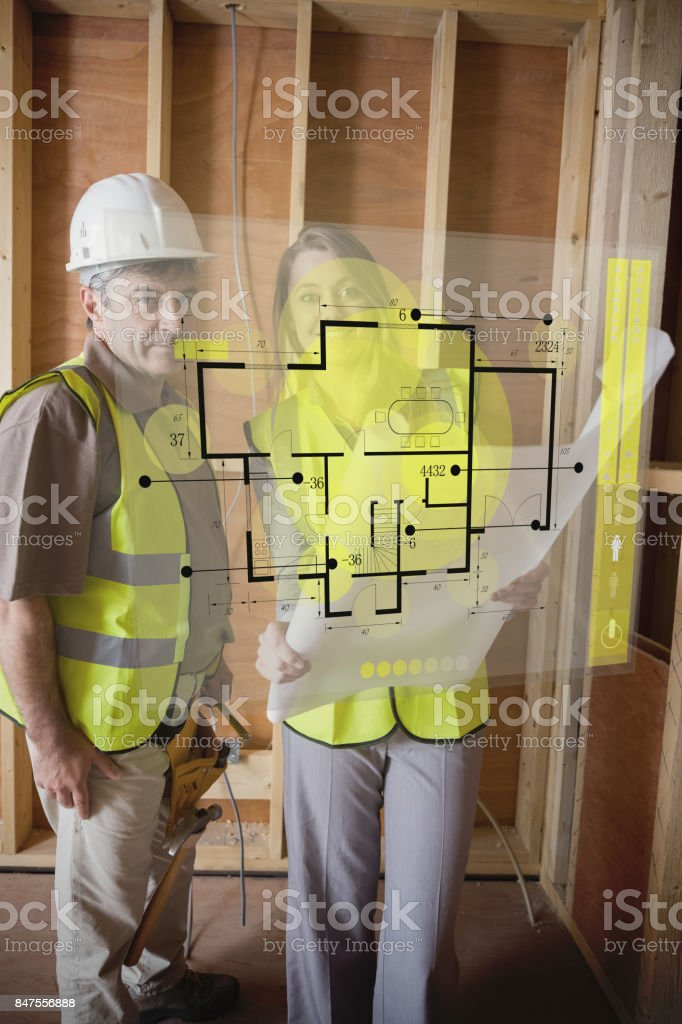 Architect and foreman checking the plans on interface stock photo