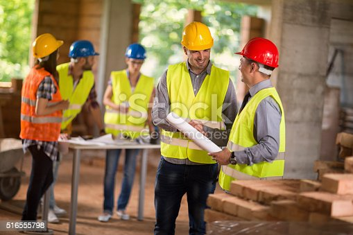 516607254istockphoto Architect and investiture handshaking on construction site 516555798
