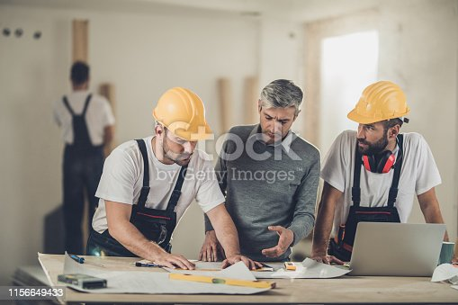 891274328 istock photo Architect and two manual workers working on housing plan at construction site. 1156649433