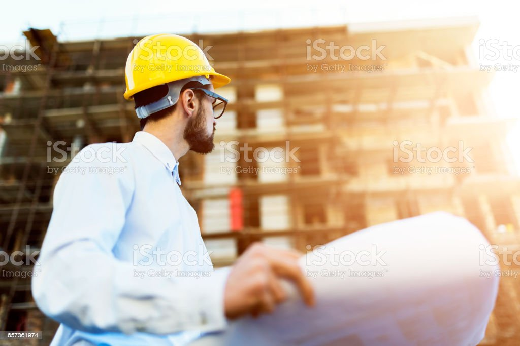 Architect at Construction Site Checking Blueprints stock photo