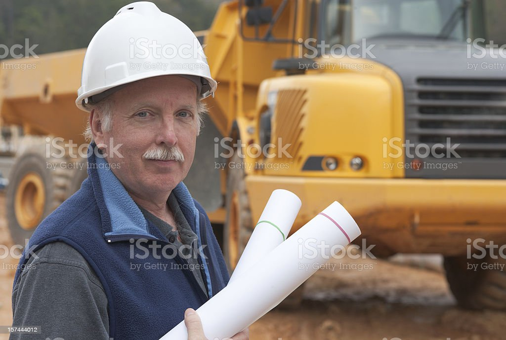 Architect at Construction site with drawings in hand  royalty-free stock photo