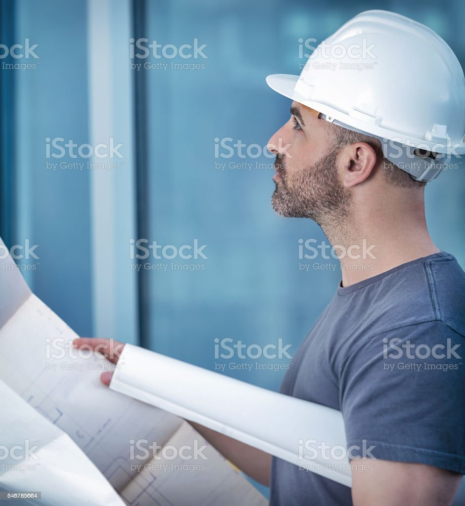 Architect builder studying layout plan of the room stock photo