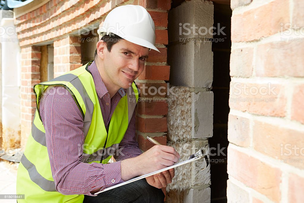 Architect Checking Insulation During House Construction stock photo