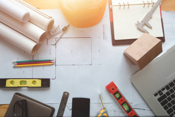 Architect concept. Architectural plans work apace top view. Architectural project, blueprints,pencil and divider compass on wooden desk table.Construction background.Engineering tools. Copy space.Architectural Concept blotter stock pictures, royalty-free photos & images