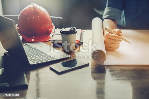istock architect design concept, Engineering hand holding pencil design building on blueprint of drawing in job site with helmet and laptop computer. 970357030