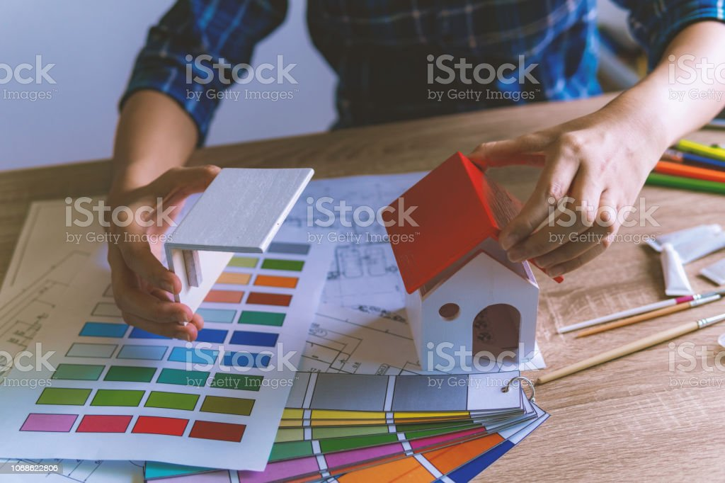 Architect design holding a home model for choosing color samples...